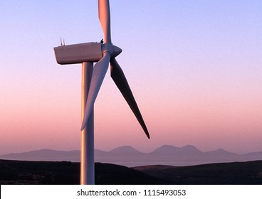 man sitting on top of a wind turbine turned pink by the setting sun; Isle of Jura in the background