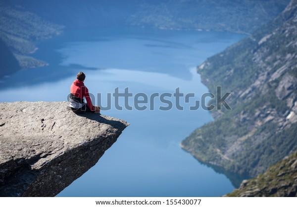 man sitting on trolltunga in norway