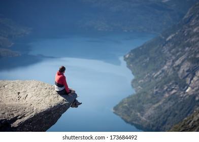 man sitting on trolltunga rock in norway