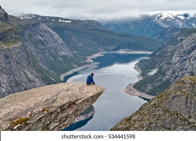 Man sitting on Trolltunga rock (Troll's Tongue rock) and looking at Norwegian mountain landscape