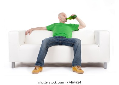 A man sitting on a white sofa, smiling and satisfied, as he holds a beer bottle.  White background
