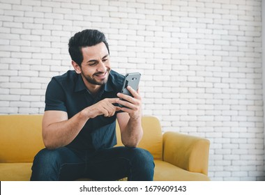 man sitting on yellow sofa using smartphone with smiling face, lifestyle concept