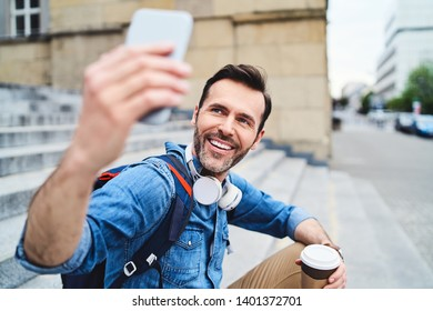 Man sitting outdoors in the city having coffee and taking selfie with smartphone