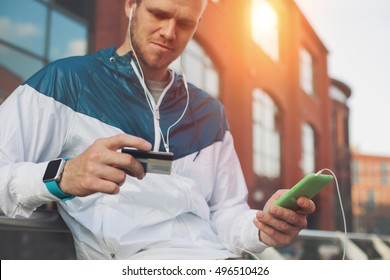 Man sitting outdoors with credit card and mobile phone, internet banking and web payment