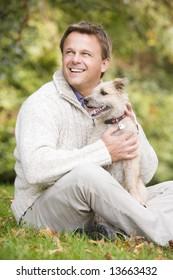 Man sitting outside holding pet dog