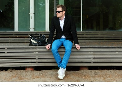A man sitting outside wearing black sunglasses and a black jacket with blue jeans.