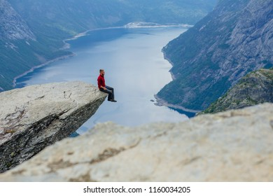 Man sitting over the precipice on trolltunga in Norway.
