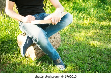 man sitting in park, reading book old
