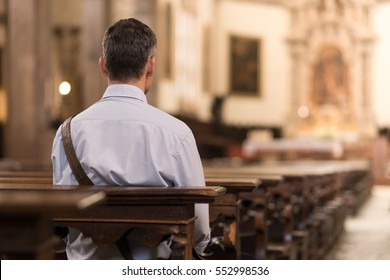 Man sitting in a pew at Church and meditating, faith and religion concept