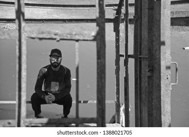 Man sitting in a place wearing caps and sunglasses black and white photo