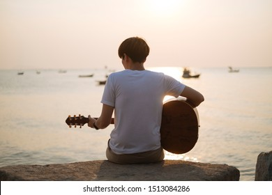 Man sitting and playing guitar on the rock at the beautiful sunset beach.