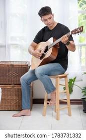 Ein Mann sitzt und spielt Gitarre auf dem Stuhl