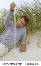Man sitting playing with sand in dunes at beach