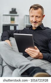 Man sitting reading a handheld tablet computer as he relaxes on a sofa in his living room in a close up cropped view