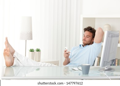 Man sitting relaxing at desk, bare feet on table, texting on mobile phone.