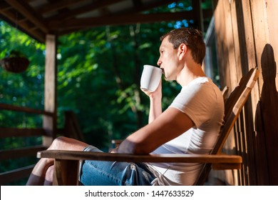 Man sitting relaxing on rocking chair on porch of house in morning wooden cabin cottage drinking coffee from cup