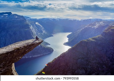 Man sitting and relaxing on trolltunga in norway