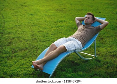 Man sitting and resting in chair on green lawn after work on vacation