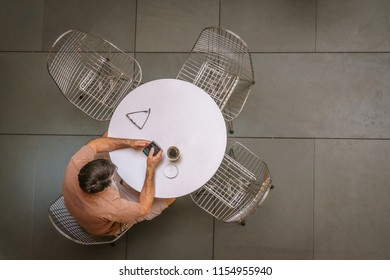 Man sitting at round white table on smart phone with coffee seen from above