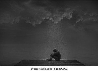 Man sitting sad at the end of a wooden bridge over the edge. Among clouds and rain during the monsoon of life/mmade picture to concept