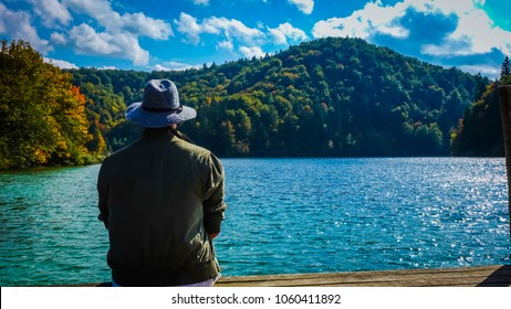 A man sitting at the shore of a lake, enjoying the mountain view at Plitvice Lakes National Park