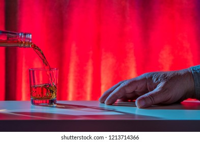 a man is sitting at a table, alcohol is poured