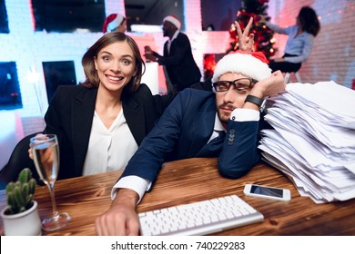 A man is sitting at a table, next to him a pile of papers. He is overwhelmed with work and bored. A colleague sits next to him and smiles. Before her is a glass of champagne. She's having fun.