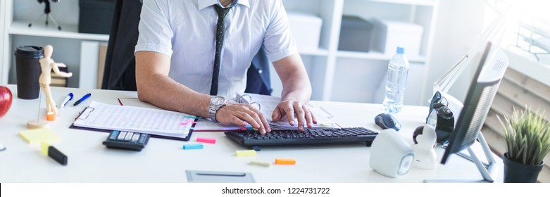 A man is sitting at a table in the office, working with documents and a computer.