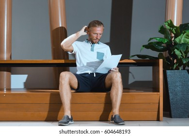 Man sitting and thinking with papers. Man with documents scratching head. Horizontal indoors shot.