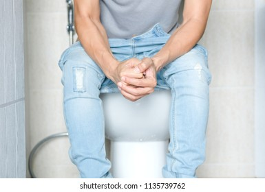 Man sitting in the toilet bowl. In the bathroom, his home is unhappy with constipation, diarrhea, food poisoning, health and medical concepts.