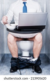 Man sitting in toilet with a laptop and a bowl of soup. / Multitasking