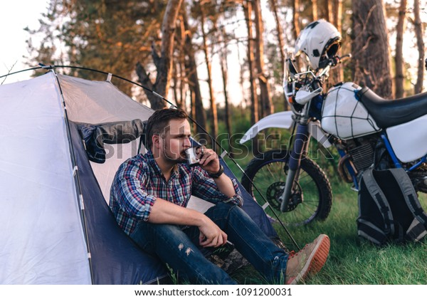 man is sitting in a tourist tent and holding metal cup in his hand, drink. Camping in forest, motorcycle touring, dual sport enduro, tent and off road adventure motorcycle, active life style concept