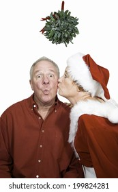 Man sitting under mistletoe being kissed by a woman in a red mrs claus, elf or pixie suit.