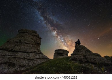 Man sitting under the stars Milky Way in the mountains silhouette rock,s inspiration photo introvert, unity the man and universe, astronomy and astrophotography