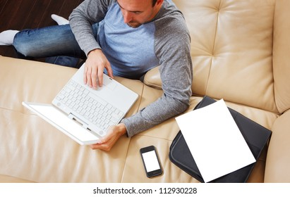 Man sitting using a modern laptop - clipping path for laptop screen, phone, and papers