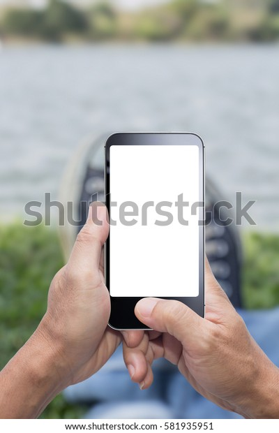 Man sitting and using smart phone on ground grasses blurred background