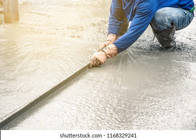 Man sitting and using a wooden spatula for cement after Pouring ready-mixed concrete on steel reinforcement to make the road by mixing mobile the concrete mixer.