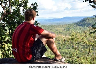 A man sitting at View point Taken at Wat Sirindhorn Wararam, Ubon Ratchathani, Thailand Taken date November 11, 2018 Dressing:Muang Thong shirt has AIA, Toshiba and Coca Cola band on and Nike pants