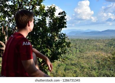 A man sitting at View point Taken at Wat Sirindhorn Wararam, Ubon Ratchathani, Thailand Taken date November 11, 2018 Dressing with Muang Thong shirt has AIA, Toshiba and Coca Cola band on