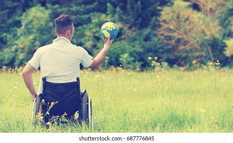 Man sitting in a wheelchair, Holding earth globe, wheelchair travel concept