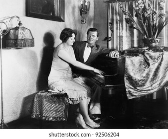 Man sitting with woman playing the piano