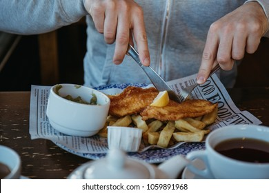 Man sitting at the wooden table, eating fish and chips, traditional English dish, tea and sauces near.