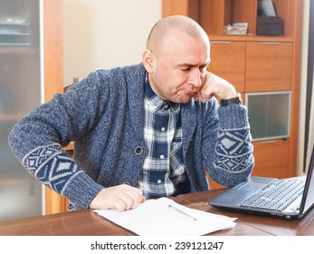 man  sitting at work on laptop at home.
