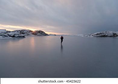 A man skating alone on the sea at sunrise. Halleviksstrand, Orust, Bohuslan, Sweden.