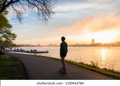 The man is skating during the sunset at Charles River Esplanade in Boston, USA