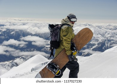 man in ski equipment, wearing safety glasses, with a backpack and snowboard in his hands rises to a snowy mountain against a cloudy sky