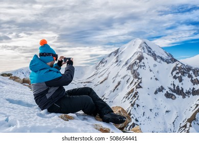 Man in ski suit taking photos of mountain landscape with smartphone.