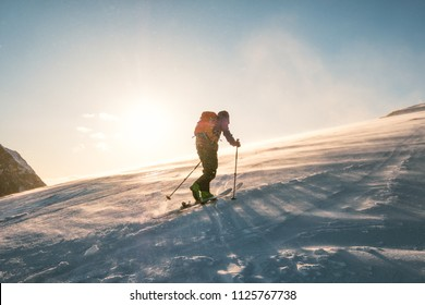 Man skier with backpack trekking on snow mountain with sunlight and storm