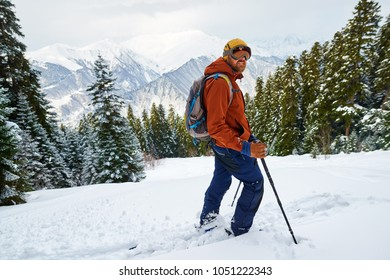 man skier in gear stands on a slope in the forest against the backdrop of mountains