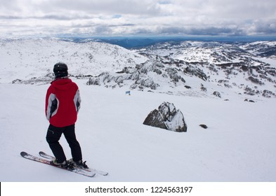 A man skier in a red jacket standing on top of the ski slope and looking towards the snow covered hills in Perisher Ski Resort, New South Wales, Australia